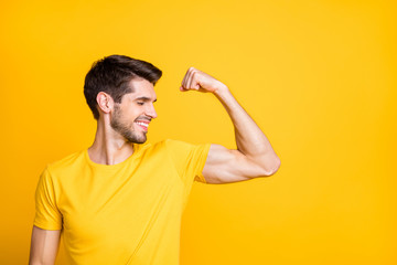 Photo of young handsome guy holding fist raised demonstrating perfect big biceps result after new sport gym wear casual t-shirt isolated yellow color background