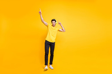 Full length body size photo of cheerful handsome attractive man wearing yellow t-shirt black trousers dancing with earphones worn isolated over vibrant color background