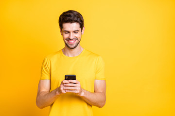 Photo of amazing handsome guy holding telephone hands chatting with friends discussing future chill students party wear casual t-shirt isolated yellow color background