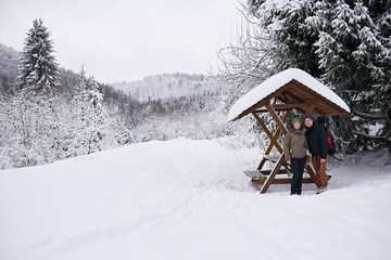Fototapete - Smiling couple standing under a shelter while hiking in winter
