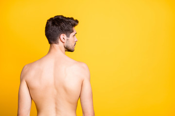 Rear behind profile view photo of handsome guy showing perfect spine muscles looking seriously empty space naked isolated yellow color background