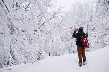 Fototapete - Hiker taking pictures of a snow covered forest in winter