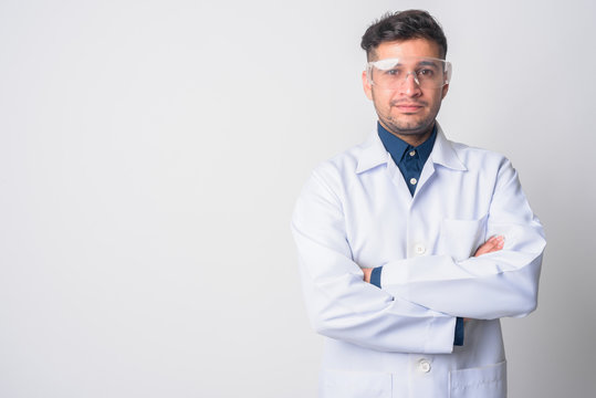 Portrait of young Persian man doctor as scientist with arms crossed