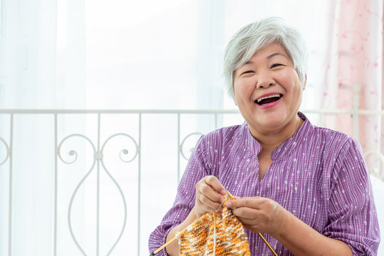 Happy senior woman female knitting at home as hobby