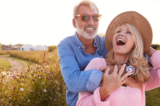 Loving Mature Couple In Countryside Hugging Against Flaring Sun