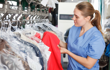 worker of laundry inspecting clothes after dry cleaning Wall mural