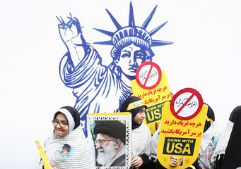 An Iranian protester holds the picture of Iranian Supreme Leader Ayatollah Ali Khamenei as they attend an anti U.S. demonstration, marking the 40th anniversary of the U.S. embassy takeover, near the old U.S. embassy in Tehran