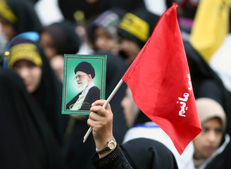An Iranian protester holds the picture of Iranian Supreme Leader Ayatollah Ali Khamenei as she attends an anti U.S. demonstration, marking the 40th anniversary of the U.S. embassy takeover, near the old U.S. embassy in Tehran