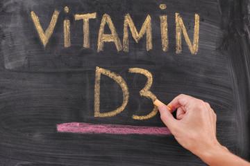 Hand writing Vitamin D3 on chalkboard