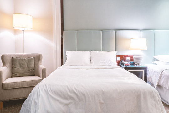 Clean and cozy modern hotel bedroom interior, warm tone room with a standing lamp, linen sofa with a cushion, design concept of luxury travel, close up.