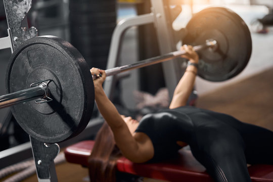 Close up of black iron barbell with heavy discs in hands of strong female weightlifter lying on red bench, attempting to do bench press in modern fitness club, side shot