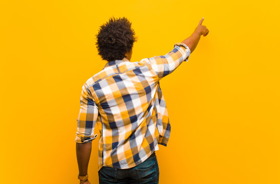 young black man standing and pointing to object on copy space, rear view against orange wall