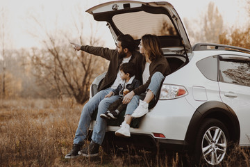 Happy family sitting at open trunk of hatchback car and pointing finger outdoors.