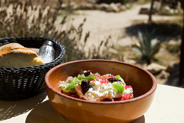 Greek Dakos, a simple fresh dish with dried bread, tomatoes, feta, or mizithra cheese, capers, oregano. In the background Donoussa Island, Greece