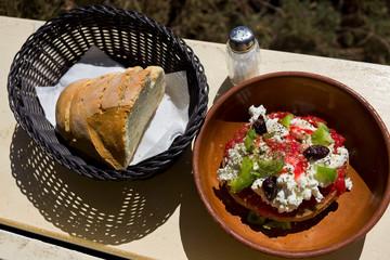 Dakos, greek vegetarian fresh dish  with dried bread, tomatoes, feta cheese, capers, oregano, salt and basket of bread. Taken in Donoussa Island, Greece