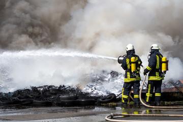 Feuerwehr löscht mit Wasser und Schaum brennende Reifen