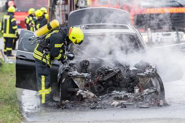 Feuerwehrmann kontrolliert mit Wärmebildkamera brennendes Auto