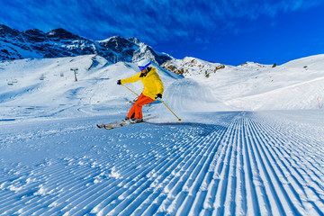 Wall Mural - Woman skiing on snow on a sunny day in the mountains. Ski in winter seasonon, the tops of snowy mountains in sunny day. South Tirol, Solda in Italy.