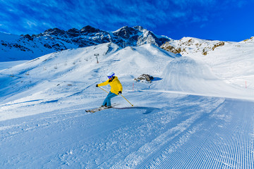 Fototapete - Woman skiing on snow on a sunny day in the mountains. Ski in winter seasonon, the tops of snowy mountains in sunny day. South Tirol, Solda in Italy.