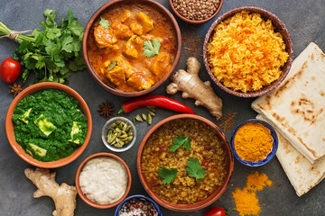 Assorted Indian food on a dark rustic background. Traditional Indian dish Chicken tikka masala, palak paneer, saffron rice, lentil soup, pita bread and spices. Top view, flat lay.