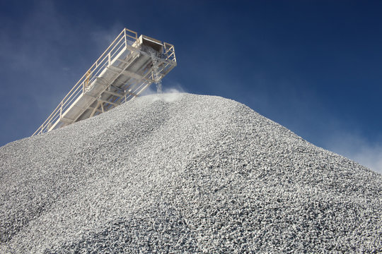 Conveyor line transporting crushed ore and pile of gravel against the blue sky, close-up. Mining industry. Mine and quarry equipment.