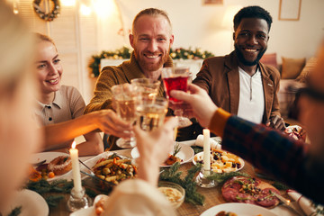 Multi-ethnic group of cheerful adult people clinking champagne glasses while enjoying Christmas...