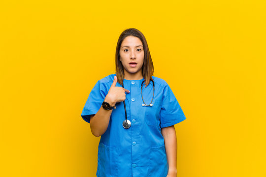 looking shocked and surprised with mouth wide open, pointing to self isolated against yellow wall