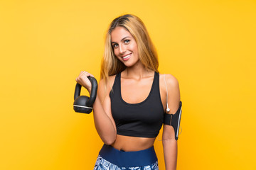 Young sport woman making weightlifting with kettlebell over isolated yellow background