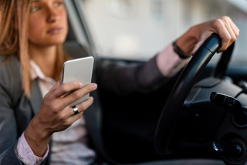 Close-up of businesswoman text messaging on cell phone while driving a car.