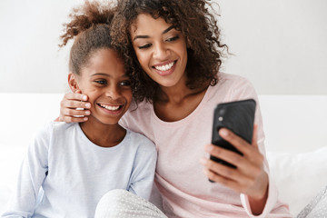Image of american woman and her little daughter using cellphone at home
