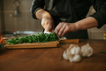 Closeup of female chef's hands preparing a recipe in the kitchen with vegetables. Woman cook...