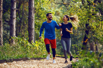 Full length of fit sporty happy caucasian couple in sportswear running in woods on trail in morning.