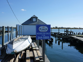 """A """"for sale"""" sign advertising an available house sits next to pilings left from a house destroyed by Hurricane Sandy in the Broad Channel neighborhood of Queens in New York City"""