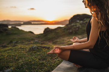 Healthy Lifestyle and Yoga Concept. Close-up hands. Woman do yoga outdoors at sunrise in lotus position. Woman exercising and meditating in morning. Nature background.