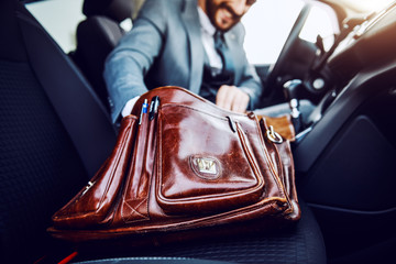 Businessman sitting in his car and taking out something from his briefcase. Selective focus on briefcase.