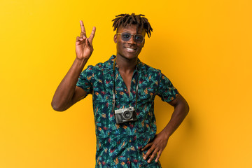 Young black rasta man wearing a vacation look joyful and carefree showing a peace symbol with fingers.