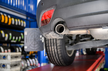 Wheel alignment, car on stand aligning for new tire replacement