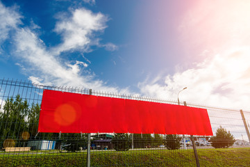 Red blank advertising banner hanging on a fence against the blue sky on a sunny day.