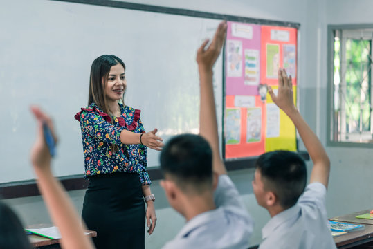 An smiling Asian female high school teacher teaches the white uniform students in the classroom by asking questions and then the students raise their hands for answers.