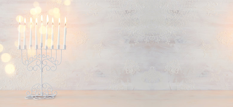 Religion image of jewish holiday Hanukkah background with menorah (traditional candelabra) and candles over white background