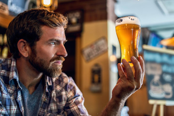 Man staring at beer glass in the bar