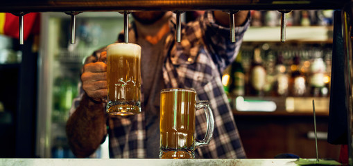 Mid section of man drawing beer from tap into a glass in the bar