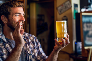 Smiling man showing ok sign while holding beer mug in the bar