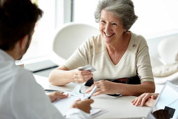Smiling senior patient with credit card talking with doctor at clinic