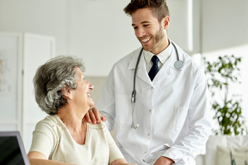 Smiling doctor consoling senior woman in clinic