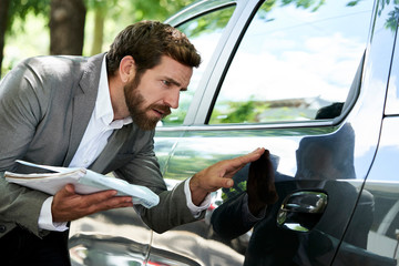 Car salesman with documents examining a car
