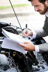 Car salesman signing documents during the car inspection