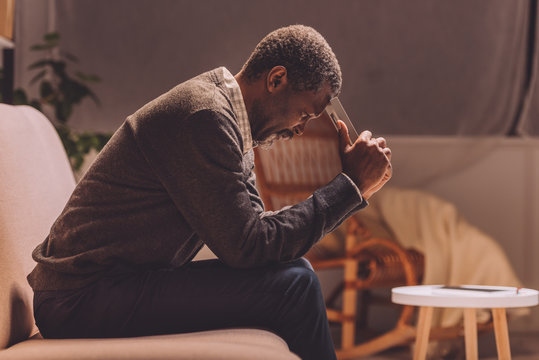 depressed african american man sitting on sofa at night and holding photo frame near head
