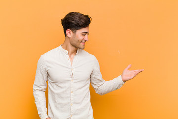 young handsome man feeling happy and cheerful, smiling and welcoming you, inviting you in with a friendly gesture against orange background Wall mural