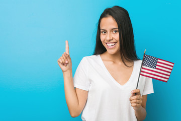 Young hispanic woman holding a united states flag smiling cheerfully pointing with forefinger away.